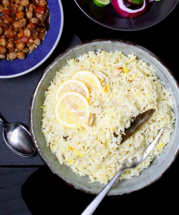 Top shot of a big bowl of jeera rice or cumin rice with chana masala in a blue bowl on the side