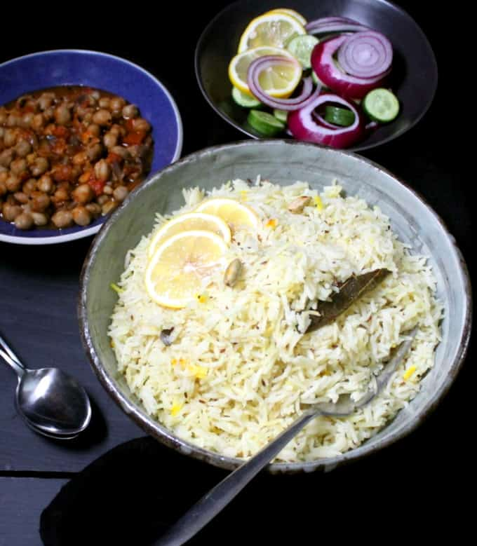 Front shot of jeera pilaf with onions and cucumbers and lemons in a black bowl and a chickpea curry next to it