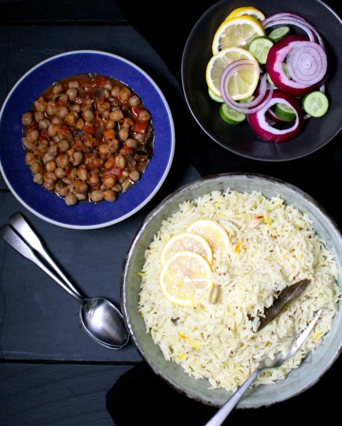 Top shot of a bowl of cumin pilaf with lemons and onions and cucumbers and chana masala on the side