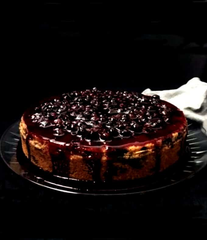 A front shot of a lemon blueberry cake with a blueberry topping dripping down the sides onto a glass plate