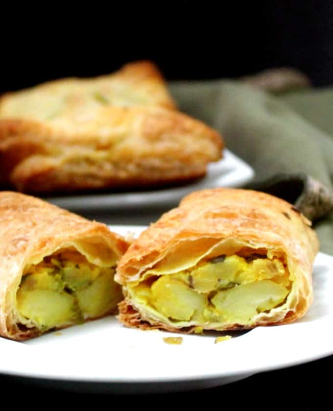 Yellow potato filling with turmeric and cumin and green chili peppers stuffed inside flaky puff pastry on a white plate