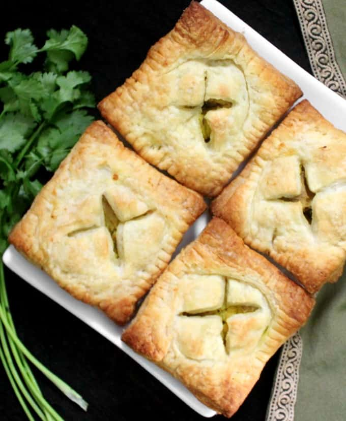 Four samosa pastry squares on a white plate with a bunch of cilantro next to them