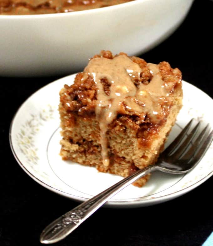 A delicious slice of vegan cinnamon roll cake with swirled cinnamon filling and a streusel topping on a white dish with a fork next to it and a baking dish with full cake in the background