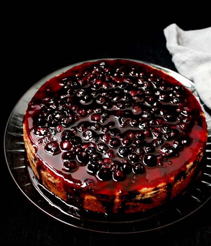 A front photo of a vegan lemon blueberry cake with blueberry topping dripping down the sides on a glass plate