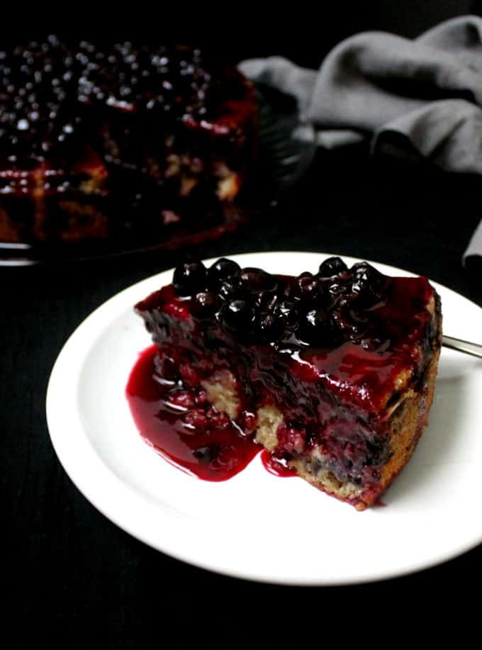 A slice of vegan lemon blueberry cake on a white plate with blueberries on top and the topping dripping down the sides and the full cake in the background