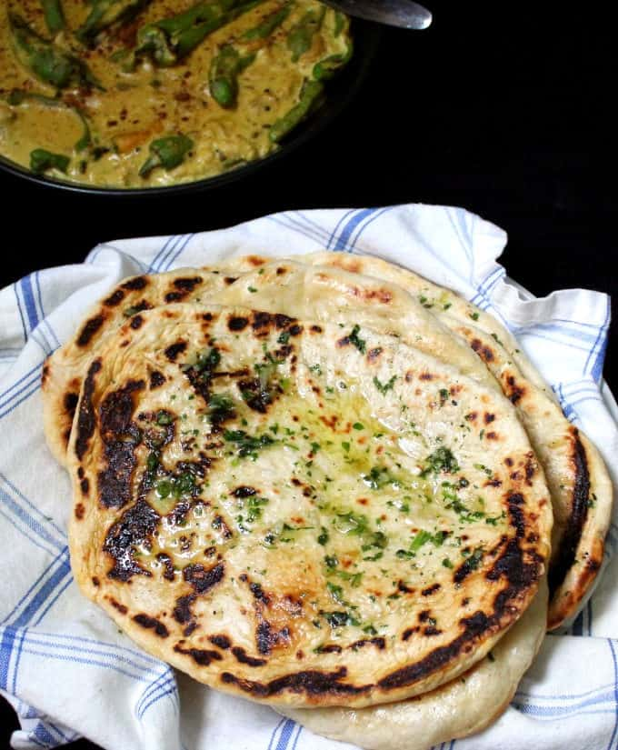 A top shot of four naan breads stacked on a napkin with a spicy yellow curry next to it