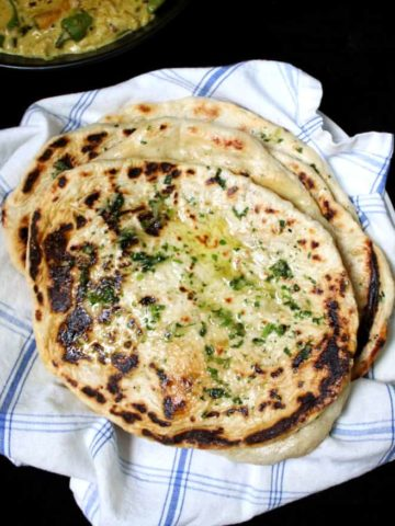 A top view of a stack of garlic butter naans with herbs scattered on top in a white and blue napkin with a yellow curry on the side