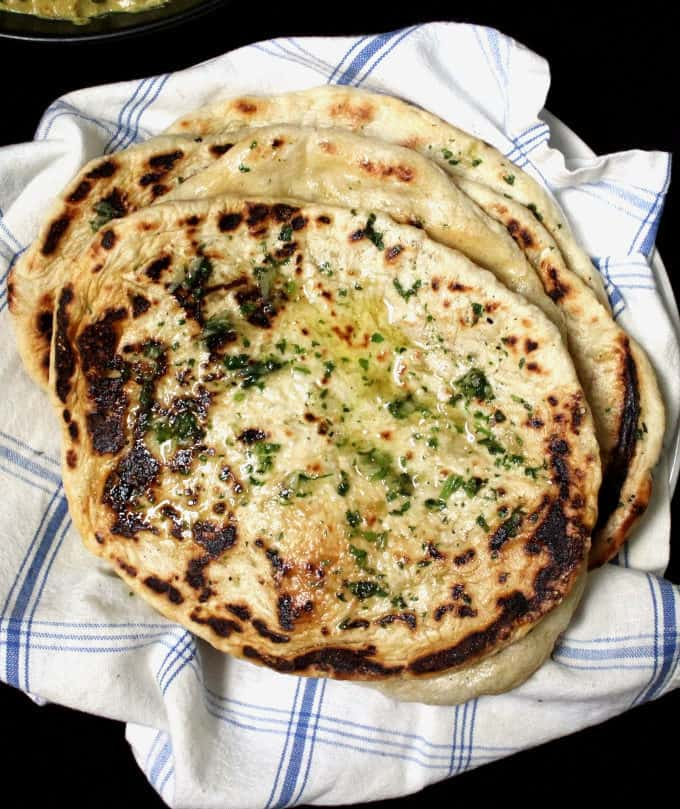 Top close up photo of a stack of garlic butter naan breads, all homemade