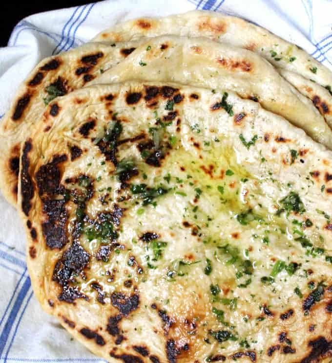 A close of of soft, puffy, hot off the griddle naan breads with herb garlic butter mixture applied to the top
