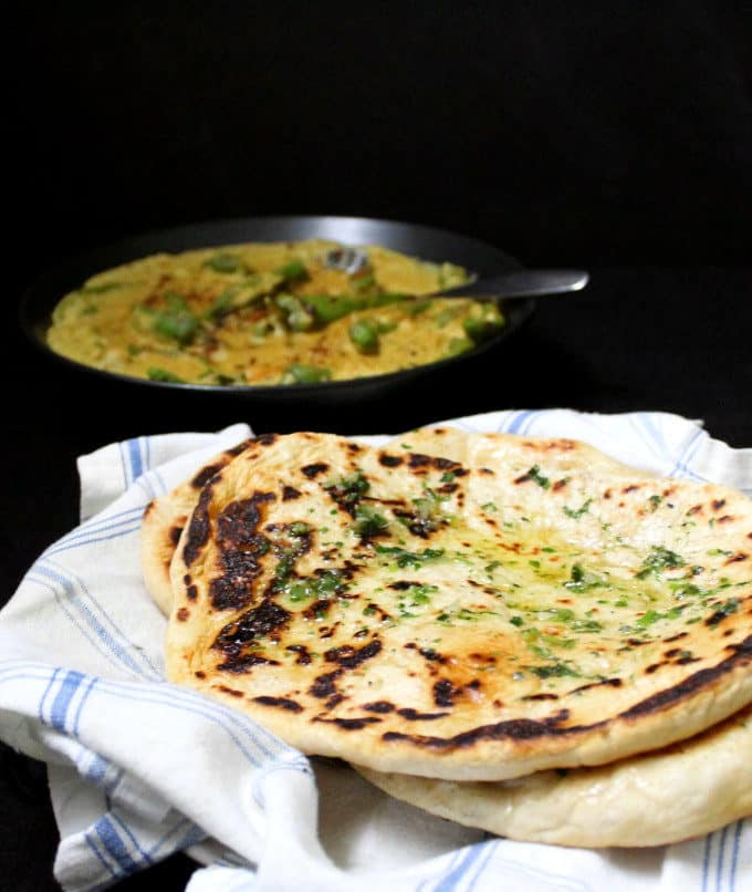 A front view of four naan breads stacked on a white plate with a blue and white napkin and a spicy curry in the background