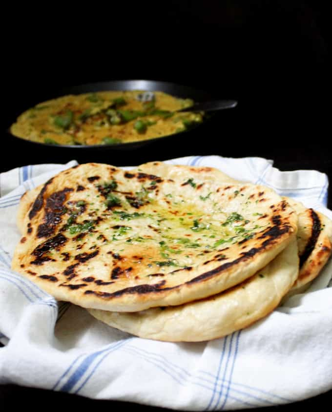 Four naan breads stacked up on a blue and white napkin with a mirch ka salan curry in the background