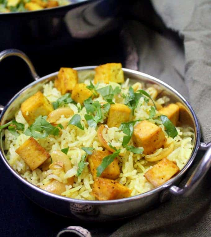 A front shot of a steel karahi bowl with lemon garlic rice, cashews, tofu and cilantro