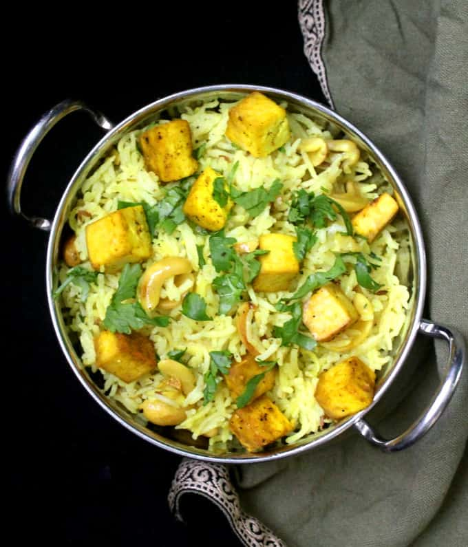 Overhead shot of lemon garlic rice with baked tofu and cilantro on a black background