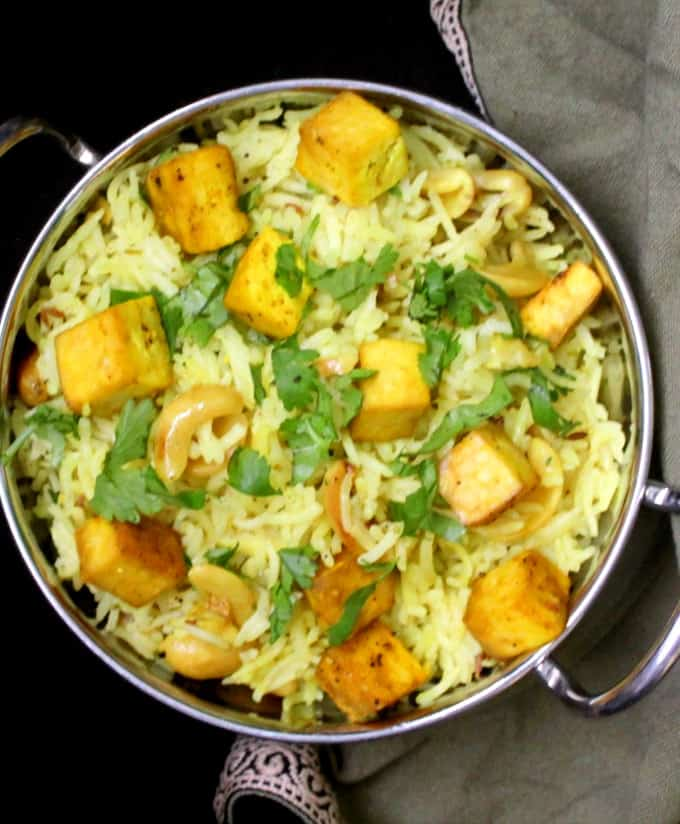 A kadhai bowl with lemon garlic rice, baked tofu cubes and cilantro and a green napkin