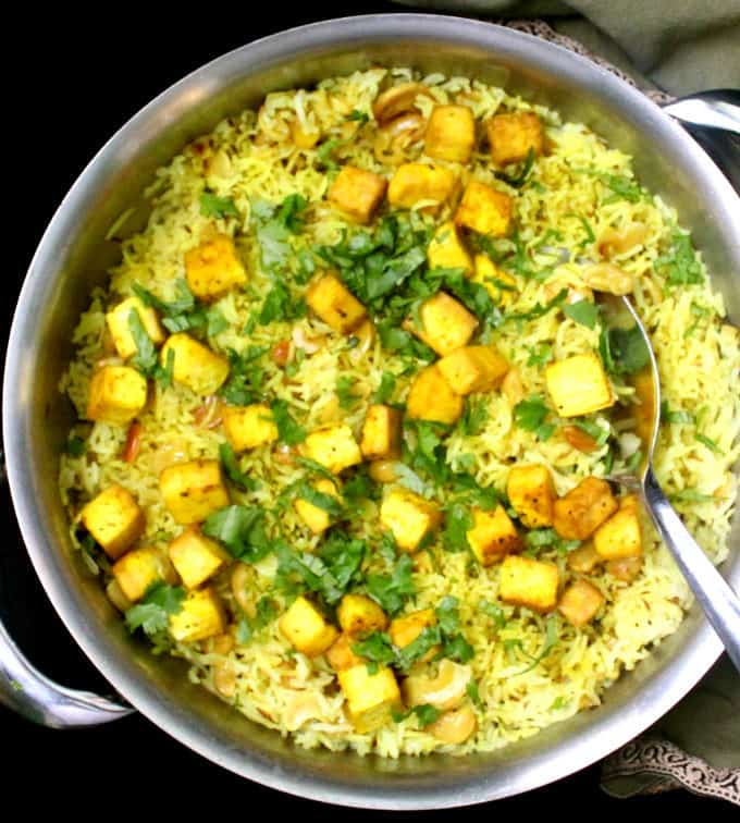 Overhead shot of a steel saucepan with lemon garlic rice, cilantro, tofu, cashews and a spoon in it