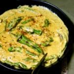 Top shot of a plate of yellow mirchi ka salan with green peppers in a black bowl