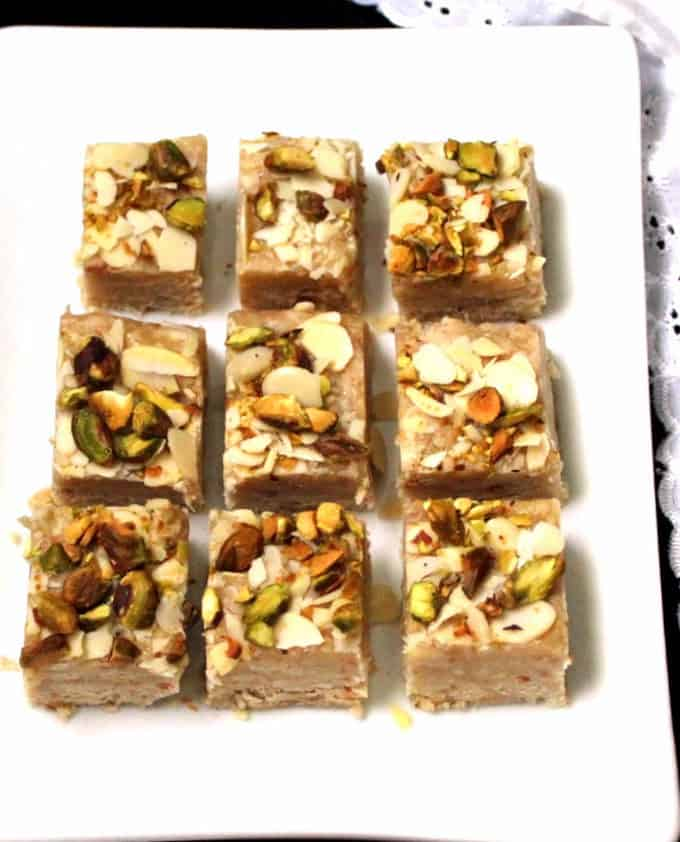 Rows of vegan barfi or burfi with nuts on top on a white plate