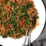 Top partial shot of a plate of dirty rice with vegan beyond meat sausage and parsley in a white platter