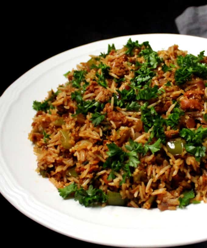 A partial shot of a white plate of dirty rice with parsley