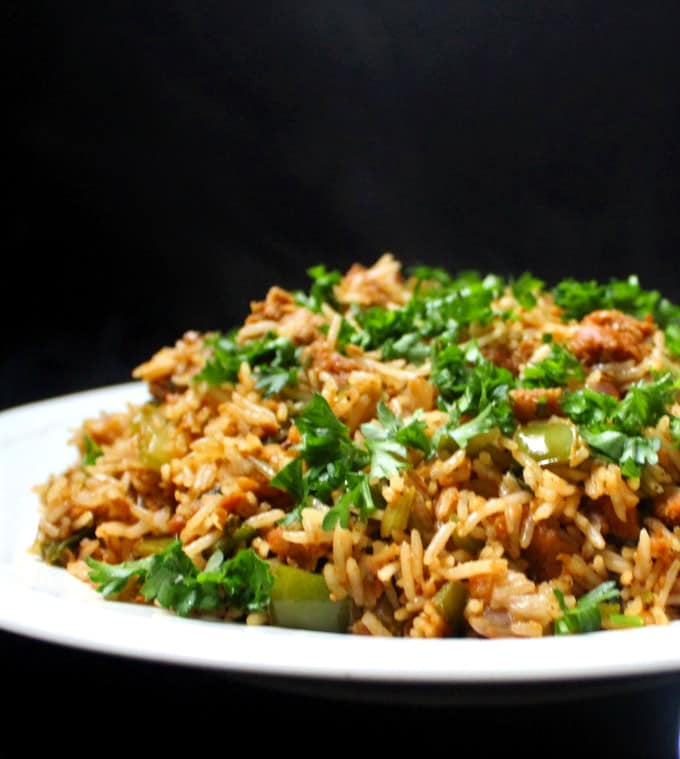 A front partial shot of a white platter filled with vegan dirty rice