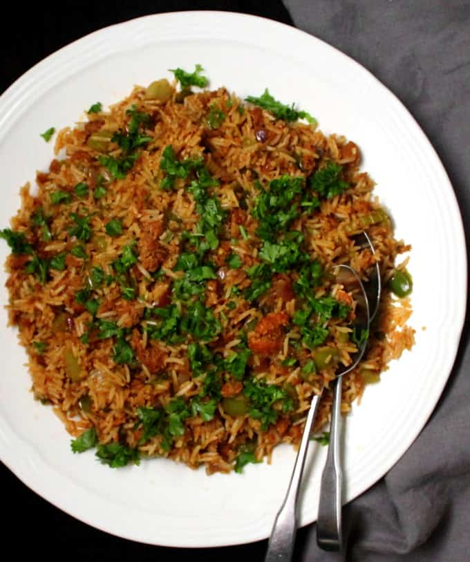 Large plate of vegan dirty rice with vegan beyond meat sausage, green bell peppers, parsley and two spoons in it