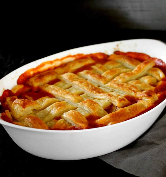 A vegan Guinness Pot pie with a golden, crispy puff pastry lattice top in a white oval baking dish