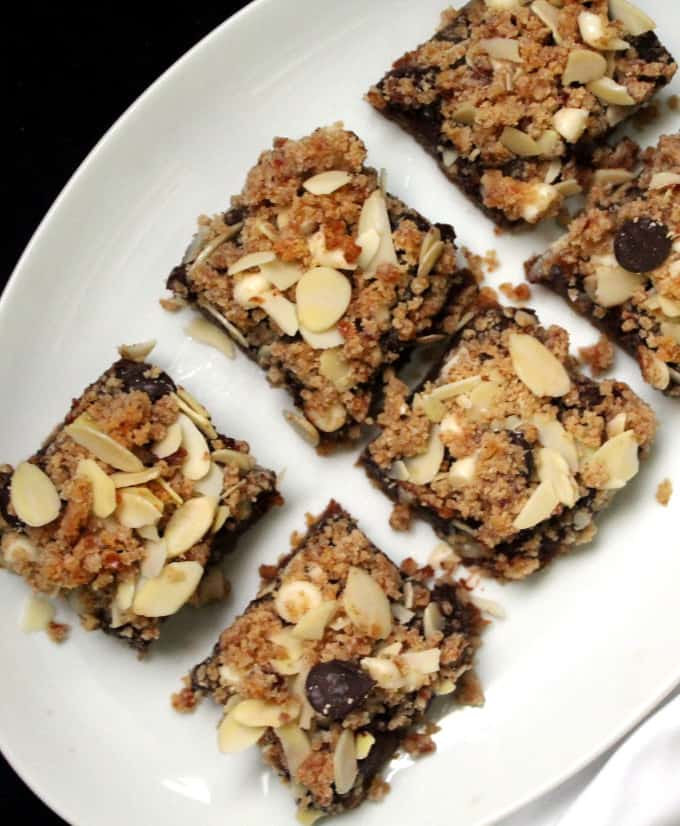 Photo of six vegan chocolate chip cookie bars on a gray plate on a black background