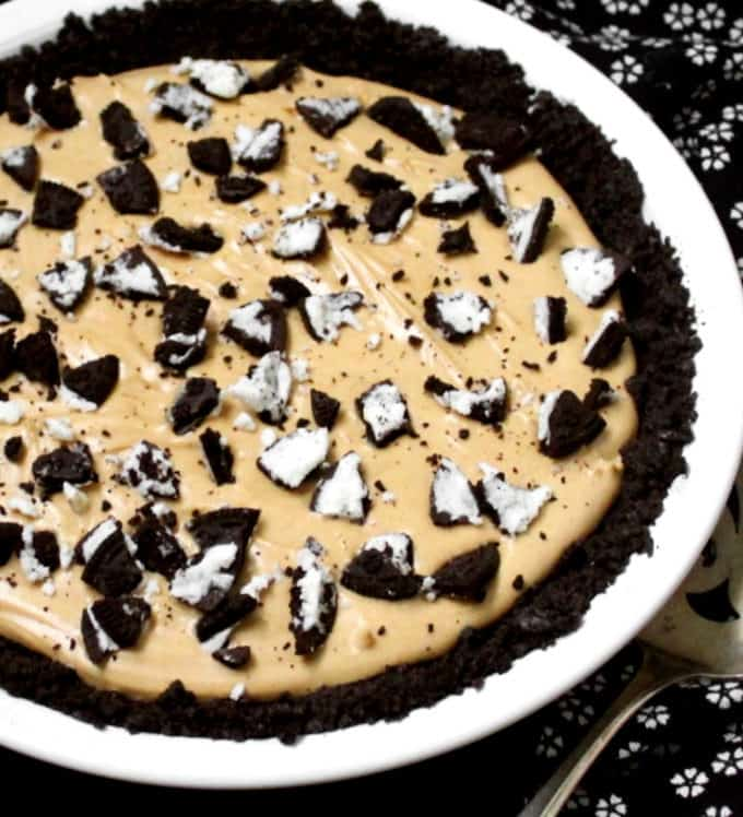 A front partial shot of a decadent peanut butter oreo pie in a white plate with cookies crumbled on top
