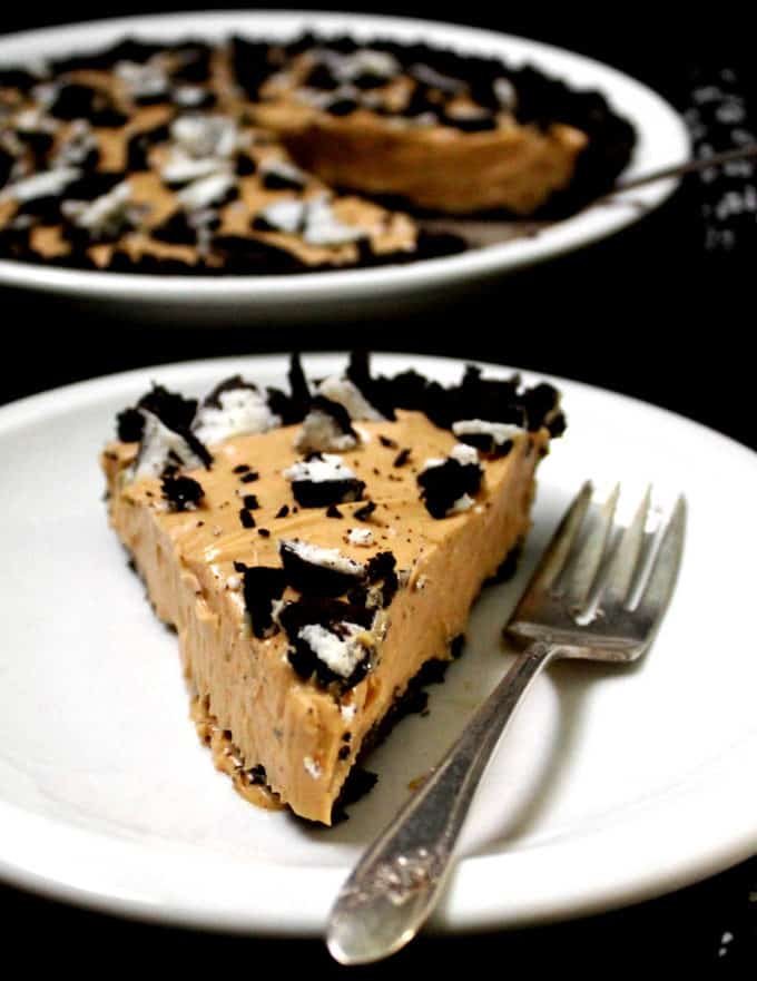 A slice of a delicious vegan peanut butter oreo pie with cookies crumbled on top, in a white plate with a fork