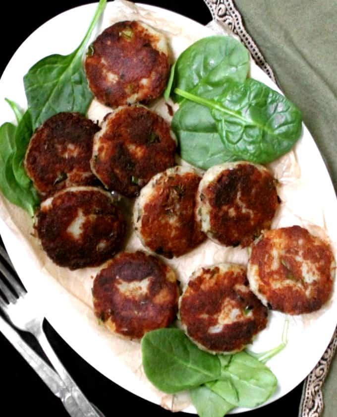 A white plate with potato kabobs or aloo tikkis