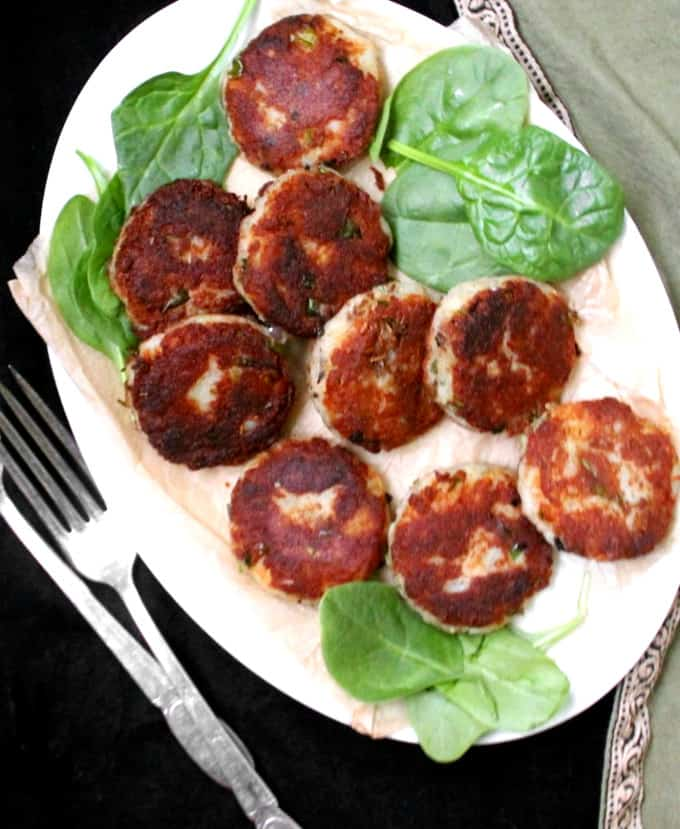 A white plate filled with aloo tikkis or aloo kabobs or potato cutlets and a few leaves of baby spinach on the side