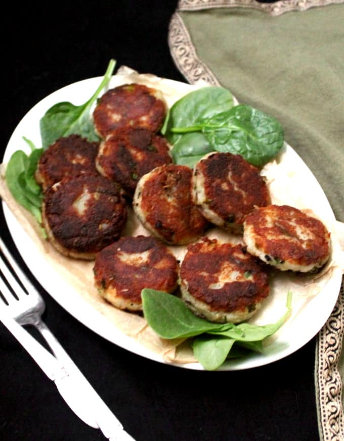 Aloo tikki on a white oval plate with greens.