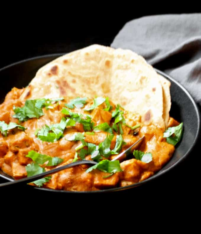 A front shot of vegan paneer butter masala with a roti folded into the black bowl and a gray napkin