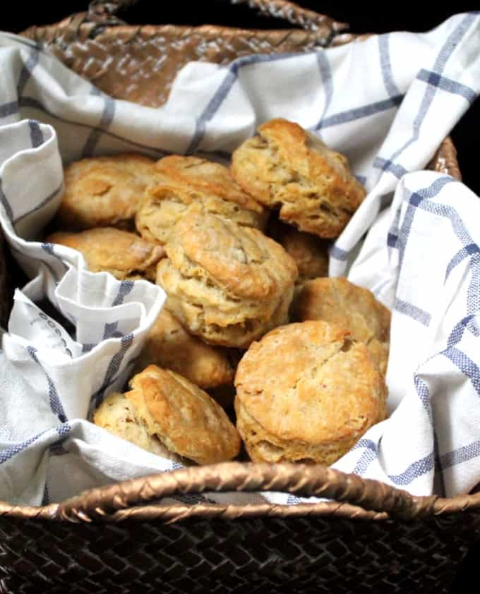 A closeup shot of golden, light, airy buttermilk biscuits nestled in a gold straw basket with a white and blue napkin