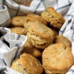 Close up shot of homemade fluffy, flaky vegan biscuits nestled in a basket
