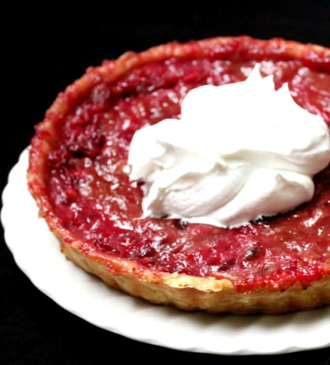 A partial shot of a vegan cranberry custard tart with whipped cream