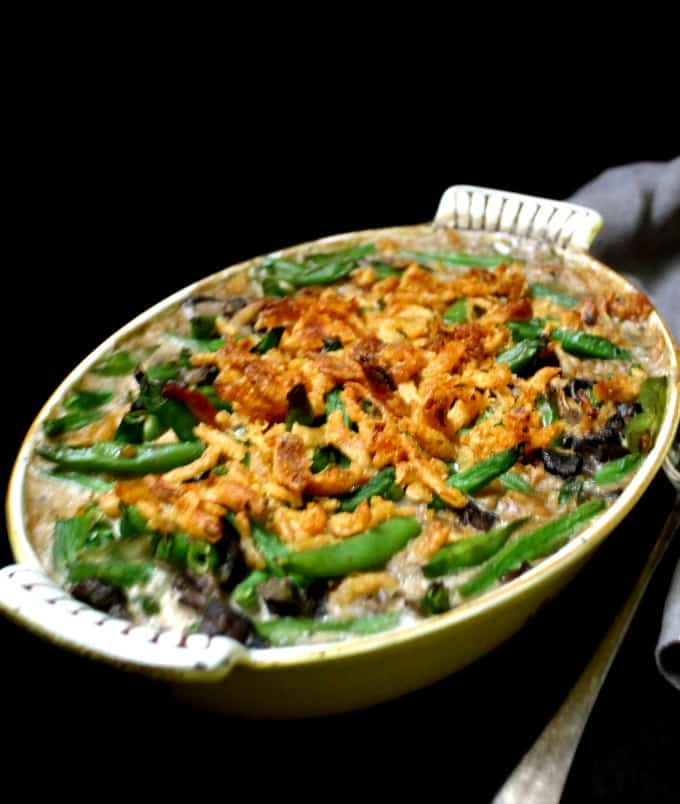 A front shot of a yellow and white baking dish with green beans casserole with a serving spoon to the side on a black table