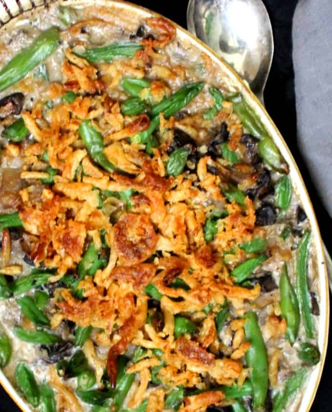 Close up shot of a creamy vegan green bean casserole with golden fried onions and cream of mushroom soup