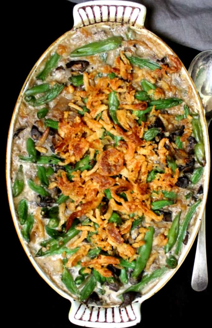 A top shot of a casserole dish with green bean casserole and fried onions with a gray napkin