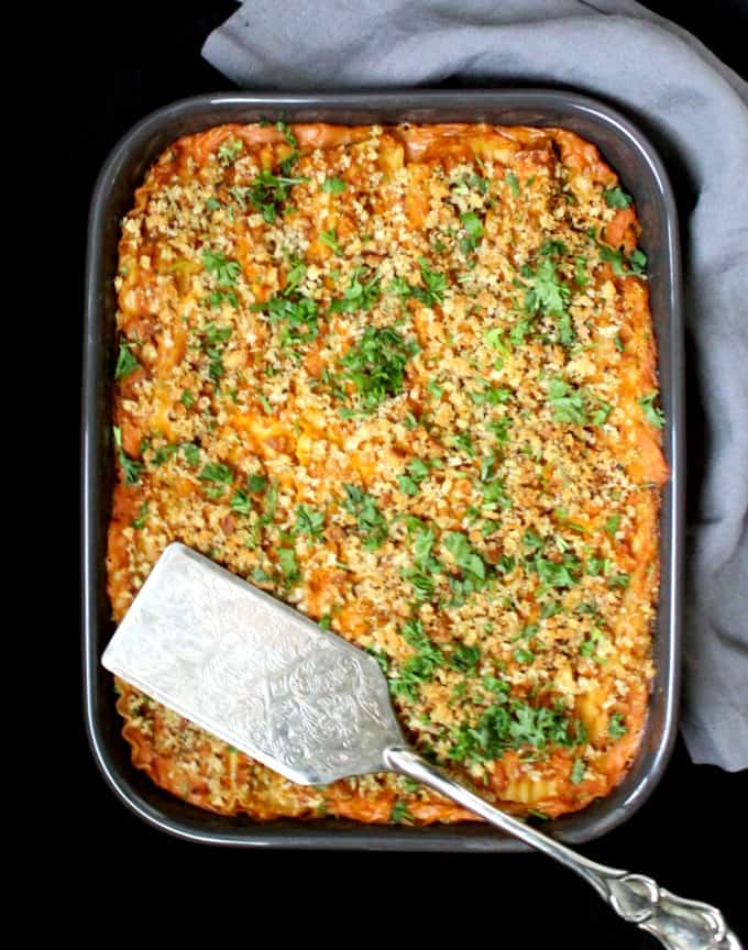 Top shot of a rectangular 9 by 13 slate gray baking dish with a vegan pumpkin spinach lasagna and a decorative silver server