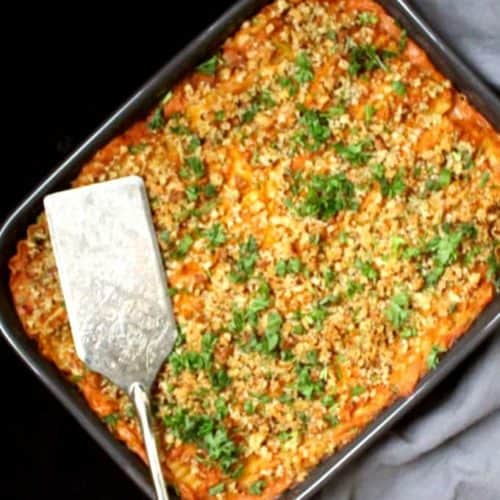 Closeup of a gray ceramic lasagna pan with a pumpkin spinach lasagna with a silver server and parsley scattered on top
