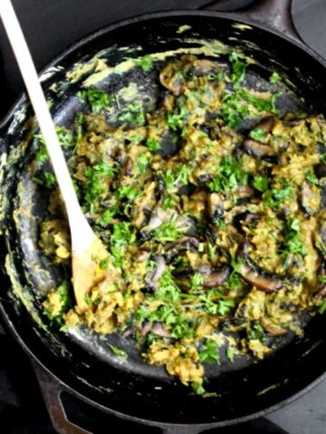 Black cast iron skillet with scrambled eggs with mushrooms and spinach and parsley