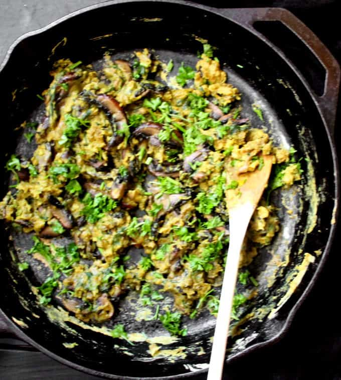 Vegan Scrambled Eggs with Mushrooms and Spinach in a black cast iron skillet with a wooden ladle