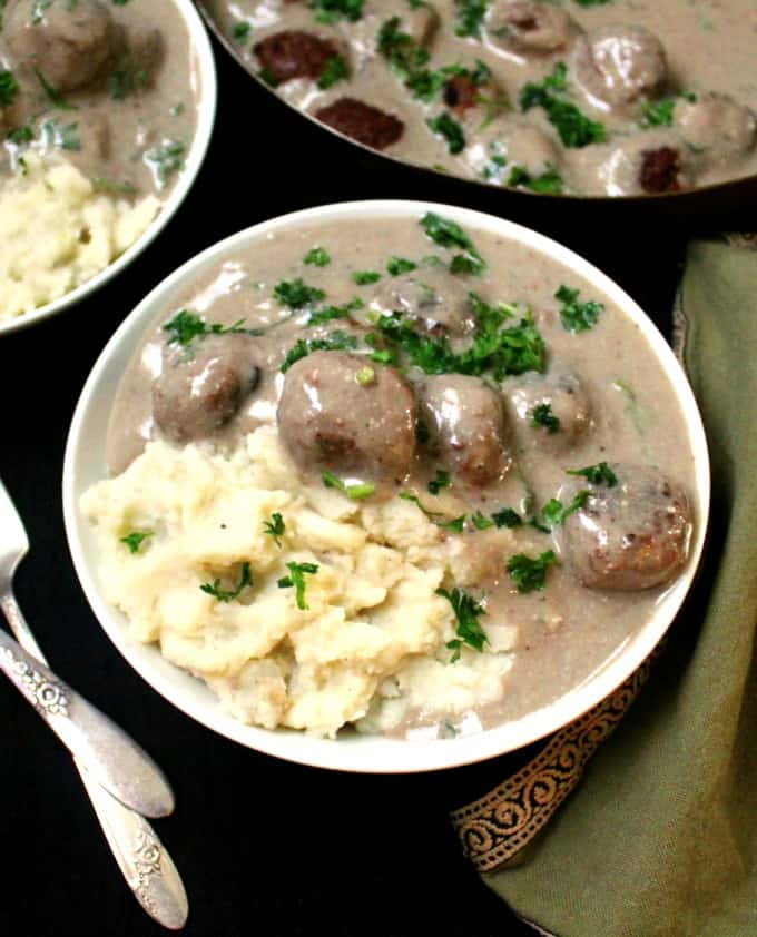 A top shot of a white bowl filled with mounds of mashed potatoes with a creamy mushroom sauce and vegan meatballs