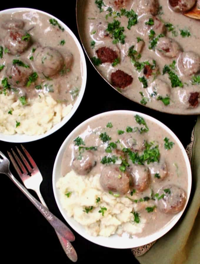 Two bowls of vegan meatballs with creamy mushroom sauce and mashed potatoes with a copper skillet and two forks