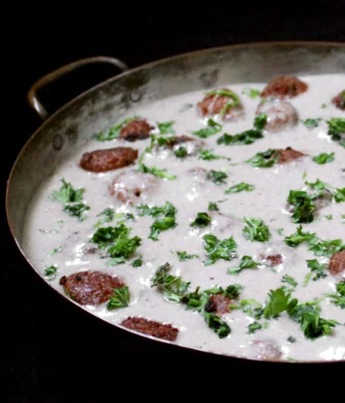 A closeup shot of creamy vegan meatballs in a mushroom sauce in a copper skillet