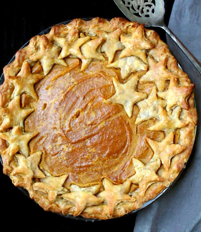 Close up partial shot of a full sweet potato pie in a glass baking dish with a gray napkin