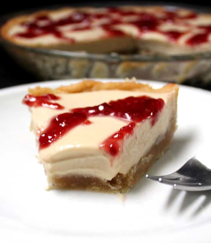 A cross section of a white chocolate silk pie with a raspberry drizzle and shortbread crust