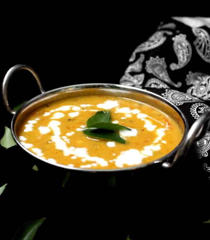 Front shot of masoor dal tadka in a karahi bowl with a black and white paisley napkin