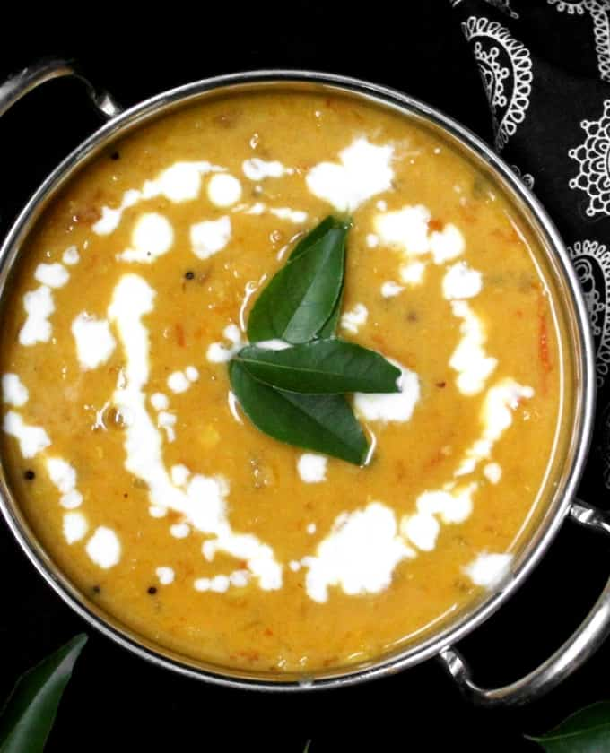 Close up of masoor dahl or dhal with coconut milk and curry leaves in a steel kadhai